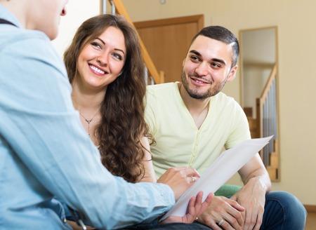 Joven pareja discutiendo los detalles positivos de los seguros privados con el agente Foto de archivo - 33459450