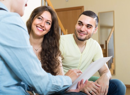 public house: Positive young couple discussing details of private insurance with agent
