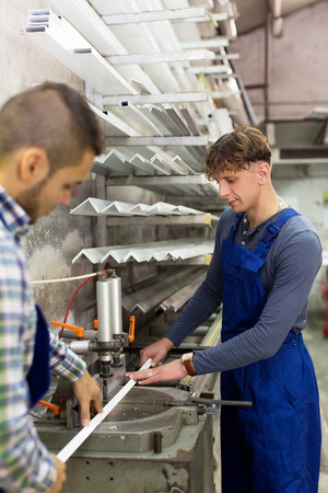 toolroom: positive european men working on a machine in plant