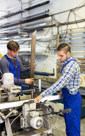toolroom: Positive males working on a machine in factory
