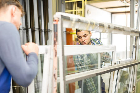Two adults working in uniform examining a window at workshop Stock Photo