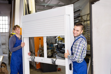 adult workers inspect the windows in the workshop photo