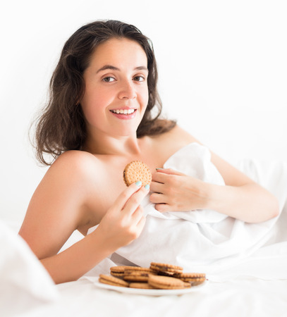 furtively: woman eating sweet chocolate chip cookies in bedroom Stock Photo