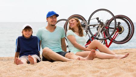 ciclos: Familia con el hijo adolescente sentado en la orilla del mar en d�a de verano con ciclos atr�s Foto de archivo