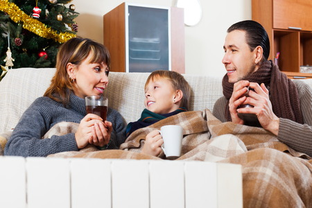Happy family with teen with heater and Christmas tree at home Stock Photo