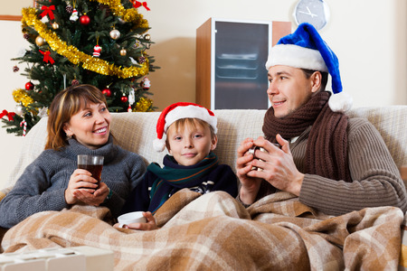 Happy family of three with cups of tea in Christmas time Stock Photo