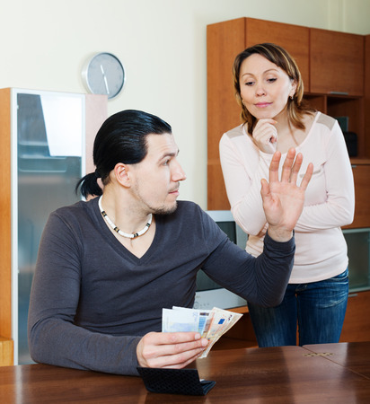rapacity: Money in family. Woman asking for money from husband in home Stock Photo