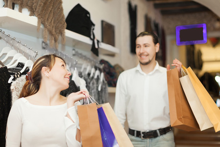 couple with shopping bags at clothing shop photo