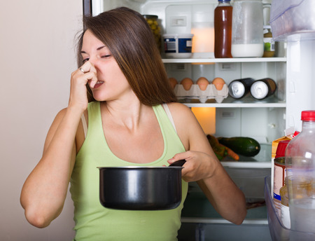 foul: Young healthy  woman holding foul food near refrigerator at home