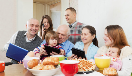 Portrait o Happy multigeneration family using electronic devices over tea  in home photo