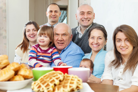 huge: Portrait of large happy three generations family sits on sofa at home together Stock Photo