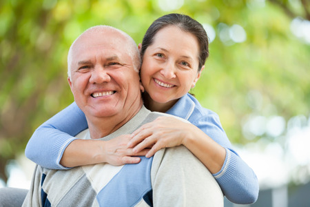 60s adult: Happy senior man and mature woman together against blured trees of park or forest