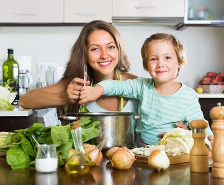 casalinga: Giovane casalinga sorridente con po 'di minestra figlia di cottura in cucina domestica Archivio Fotografico