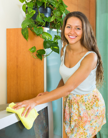 televisor: Happy smiling girl cleaning TV with rag at home Stock Photo