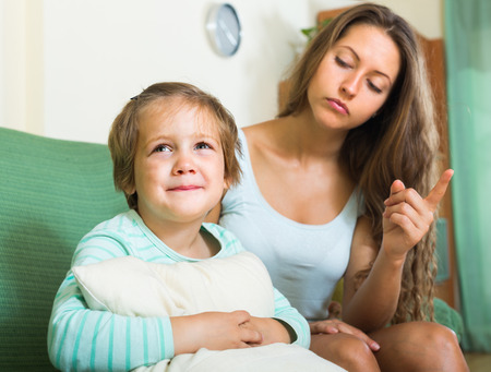 berate: Young woman berating crying child in home interior. Focus on girl Stock Photo