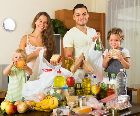 common market: Smiling young family with two children came back from supermarket Stock Photo