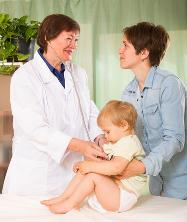 auscultoscope: Mature doctor examing baby  with stethoscope at clinic Stock Photo