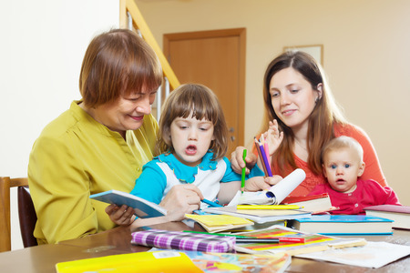 Happy woman with adult daughter and two children playing at home interior photo