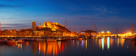 Panorama of port with yachts against Castle of Santa Barbara in night. Alicante, Spain