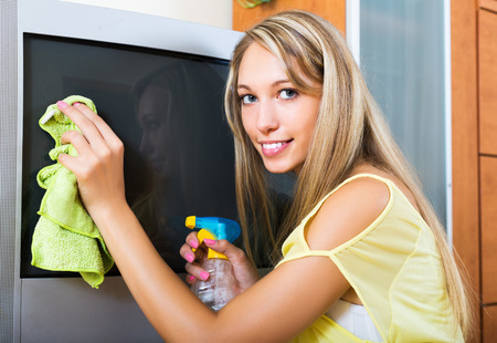 televisor: Blonde positive housewife cleaning TV with rag at home Stock Photo