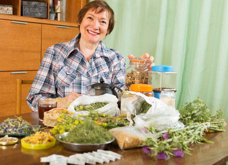 Elderly woman sitting at table with aroma herbs and smiling