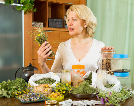 heterogeneous: Mature woman sitting at table with aroma herbs in home interior