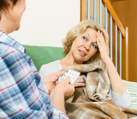 soporific: Two mature women with pill on couch indoor