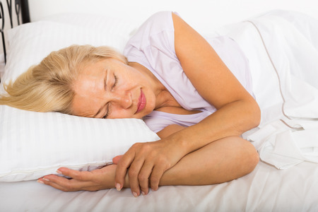 sleeping rooms: Blonde mature woman sleeping on white pillow in bed at home