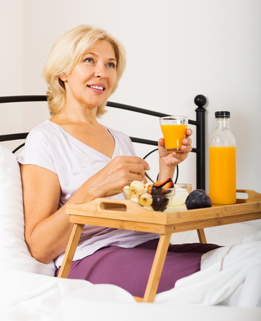 Mature woman having breakfast  at overbed table in bed photo