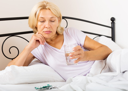 50 60 years: mature lady with pills and vitamins in bed Stock Photo