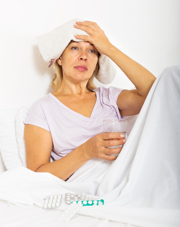complications: Female pensioner laying in bed with towel on forehead at bedroom Stock Photo
