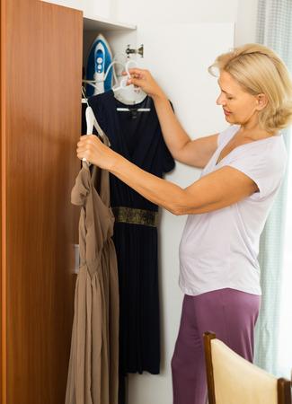 Mature femme blonde choisissant robe dans une armoire à son domicile