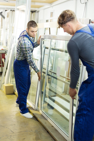 Two workers in uniform inspecting windows at workshop Stock Photo