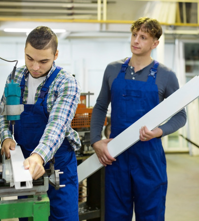 skilled operator: Couple working near the machine made product Stock Photo