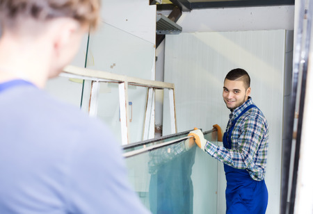 glasswear: Two careful workmen working with glass for windows at workshop Stock Photo