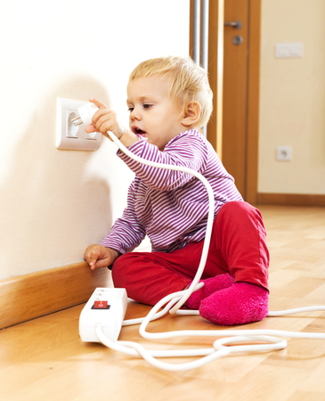riskiness: Baby girl playing with electrical extension Stock Photo