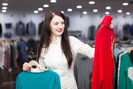 'pull over': happy woman choosing sweater at clothing shop