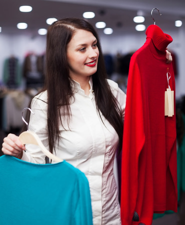 clothing store: Smiling woman choosing sweater at clothing store