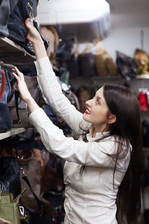 vanity bag: cheerful woman chooses bag at shop Stock Photo