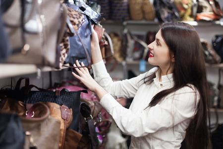 vanity bag: cheerful girl chooses bag at shop Stock Photo