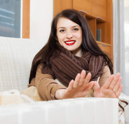 Portrait of woman  in scarf  warming near warm heater  in home Stock Photo