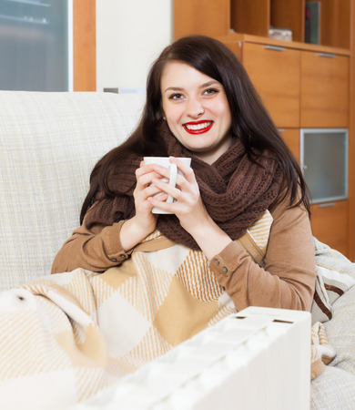 Happy woman  with cup near  electric heater in home Stock Photo