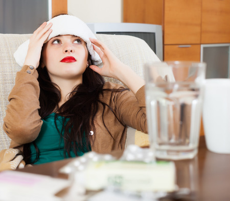 Suffering woman  stuping  towel to her head