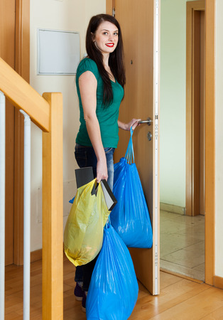 Brunette woman putting out the garbage at home photo