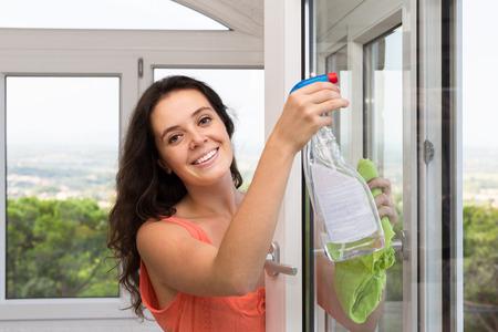 atomizer: Smiling woman cleaning windows using atomizer indoor