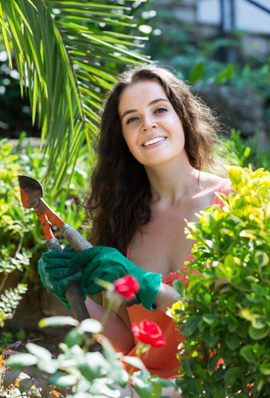 pruning scissors: Happy smiling young woman working with pruning scissors in the garden