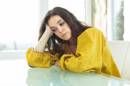 femme triste: Jeune femme en blouse lumineuse ennuyer à la maison