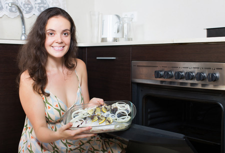 panful: Smiling woman putting  fish in oven at home kitchen