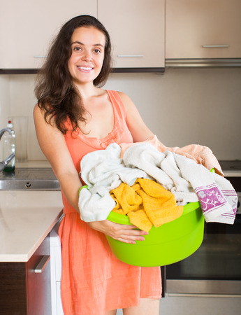 stereotypical: Home laundry. Smiling young housewife with linen basket near washing machine