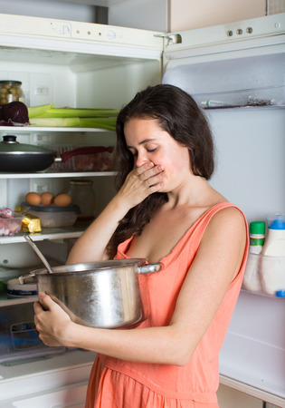 foul: Young woman holding foul food near refrigerator at home